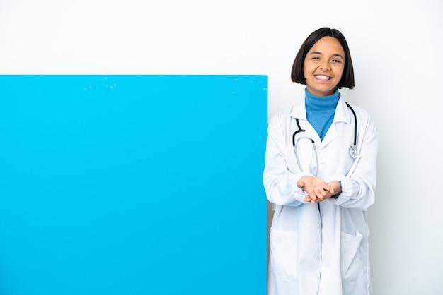 Giovane donna medico di razza mista con un grande cartello isolato tenendo copyspace immaginario il palmo per inserire un annuncio