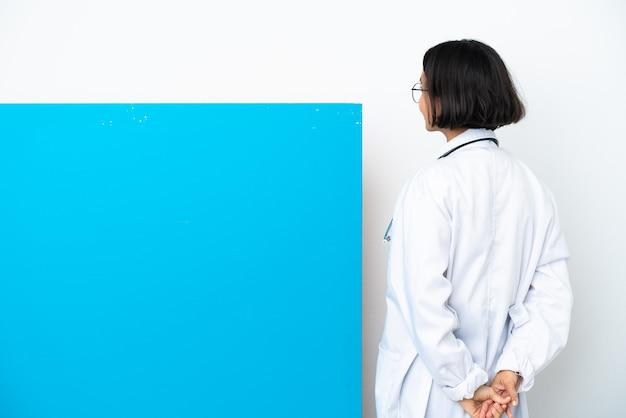 Giovane donna medico di razza mista con un grande cartello isolato su sfondo bianco in posizione posteriore e guardando indietro