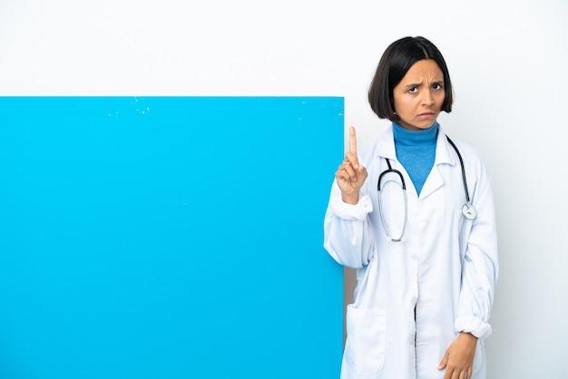Giovane donna medico di razza mista con un grande cartello isolato su sfondo bianco contando uno con espressione seria