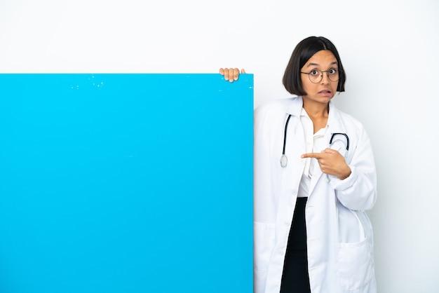 Giovane donna medico di razza mista con un grande cartello isolato su sfondo bianco spaventato e rivolto di lato