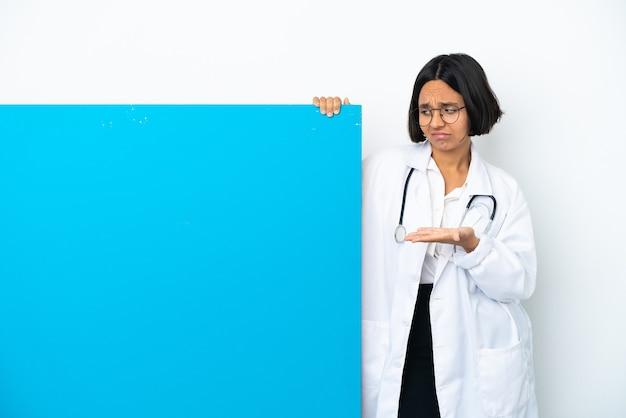 Giovane donna medico di razza mista con un grande cartello isolato su sfondo bianco che tiene copyspace con dubbi