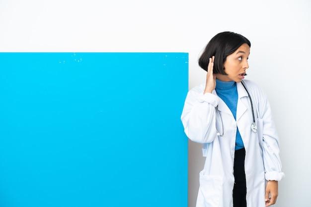 Giovane donna medico di razza mista con un grande cartello isolato su sfondo bianco ascoltando qualcosa mettendo la mano sull'orecchio