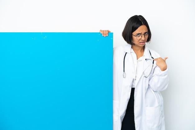 Giovane donna medico di razza mista con un grande cartello isolato su sfondo bianco che punta a se stessi