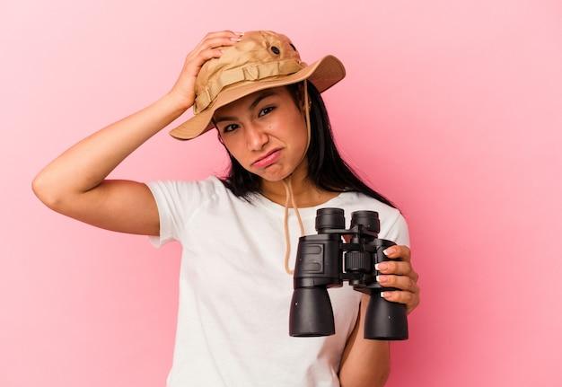 Giovane donna esploratrice di razza mista che tiene in mano un binocolo isolato su sfondo rosa scioccata, ha ricordato un incontro importante.