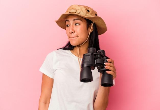 Giovane donna esploratrice di razza mista che tiene in mano un binocolo isolato su sfondo rosa confuso, si sente dubbiosa e insicura.