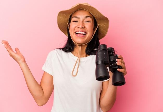 Giovane donna esploratrice di razza mista con binocolo isolato su sfondo rosa che riceve una piacevole sorpresa, eccitata e alzando le mani.