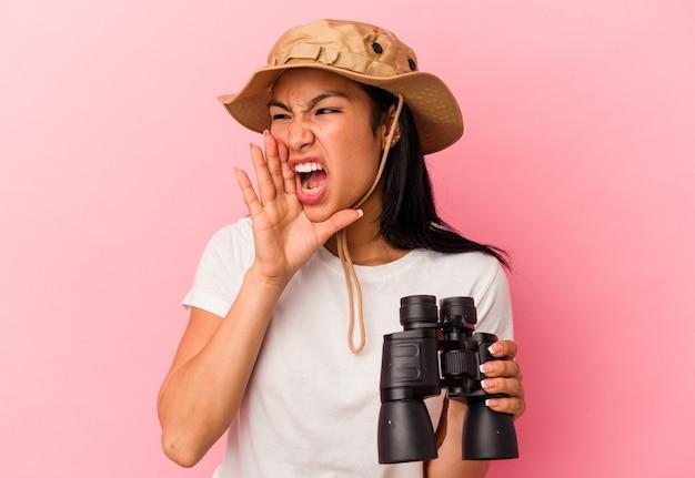 Giovane donna esploratrice di razza mista che tiene in mano un binocolo isolato su sfondo rosa che grida e tiene il palmo vicino alla bocca aperta.