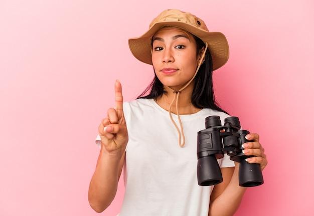 Giovane esploratore di razza mista che tiene in mano un binocolo isolato su sfondo rosa che mostra il numero uno con il dito.