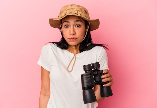 La giovane donna dell'esploratore della corsa mista che tiene il binocolo isolato su fondo rosa alza le spalle e apre gli occhi confusi.