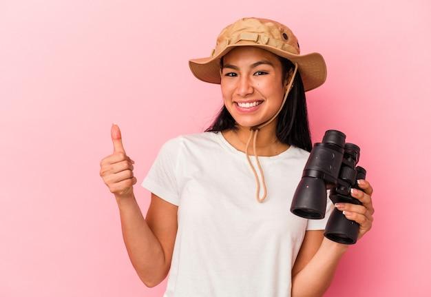 Giovane donna dell'esploratore della corsa mista che tiene il binocolo isolato su fondo rosa che sorride e che alza pollice su