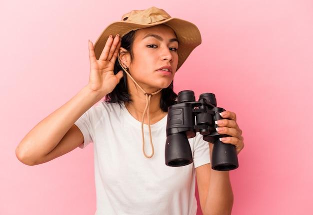 Giovane donna dell'esploratore della corsa mista che tiene il binocolo isolato su fondo rosa che prova ad ascoltare un gossip.