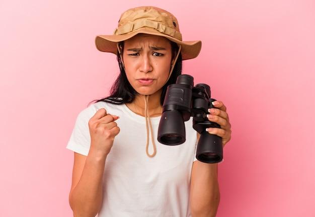 Giovane donna dell'esploratore della corsa mista che tiene il binocolo isolato sulla parete rosa che mostra pugno