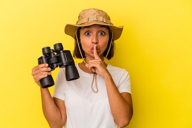 Giovane donna esploratrice di razza mista che tiene in mano un binocolo isolato su sfondo giallo mantenendo un segreto o chiedendo silenzio.