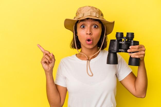 Giovane donna dell'esploratore della corsa mista che tiene il binocolo isolato su fondo giallo che indica il lato