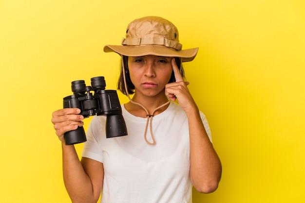 Giovane donna esploratrice di razza mista con binocolo isolato su sfondo giallo che punta il tempio con il dito, pensando, concentrato su un compito.