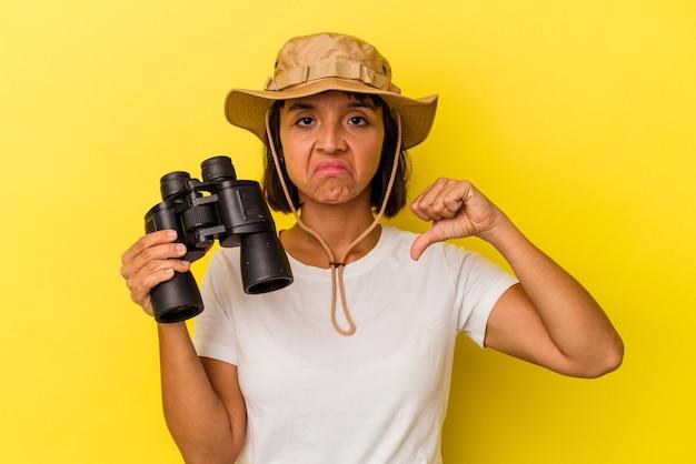 Giovane donna esploratrice di razza mista che tiene in mano un binocolo isolato su sfondo giallo che mostra un gesto di antipatia, pollice in giù. concetto di disaccordo.