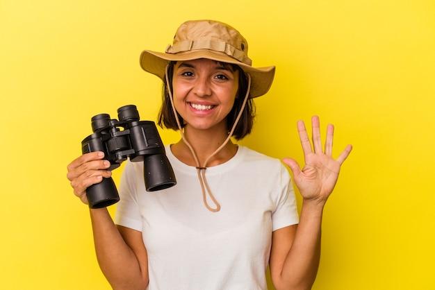 Giovane donna esploratrice di razza mista che tiene il binocolo isolato su sfondo giallo sorridente allegro che mostra il numero cinque con le dita.