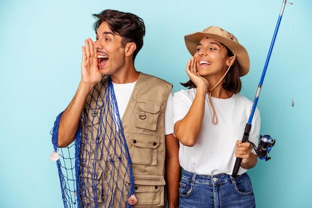 Giovane coppia di pescatori di razza mista isolata su sfondo blu che grida e tiene il palmo vicino alla bocca aperta.