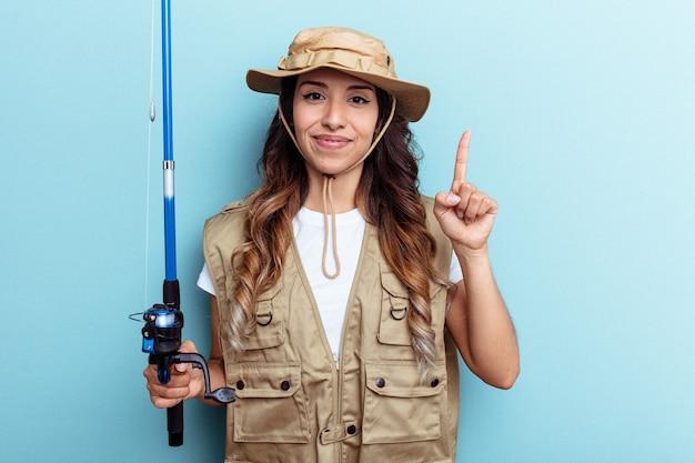 Giovane pescatrice della corsa mista che tiene un'asta isolata su fondo blu che mostra il numero uno con il dito.