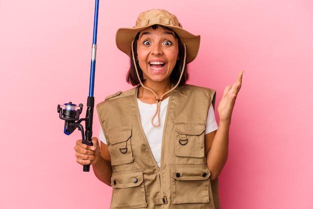 Giovane pescatrice di razza mista che tiene una canna isolata su sfondo rosa ricevendo una piacevole sorpresa, eccitata e alzando le mani.