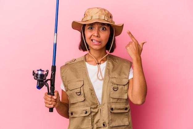 Giovane pescatrice di razza mista che tiene una canna isolata su sfondo rosa che mostra un gesto di delusione con l'indice.