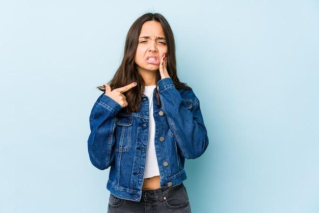 Giovane donna ispanica di razza mista isolata con un forte dolore ai denti, dolore molare.
