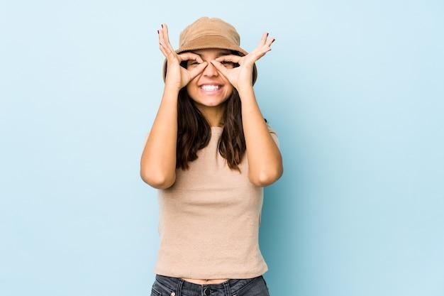 Giovane donna ispanica di razza mista isolata che mostra il segno giusto sugli occhi