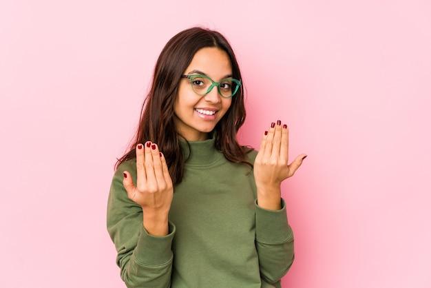 Giovane donna ispanica di razza mista che punta il dito contro di te come se invitando ad avvicinarsi.