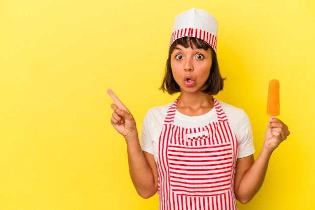 Giovane gelatiera di razza mista che tiene in mano un gelato isolato su sfondo giallo rivolto verso il lato
