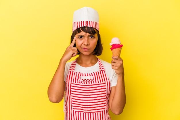 Giovane gelatiera di razza mista che tiene in mano un gelato isolato su sfondo giallo indicando il tempio con il dito, pensando, concentrato su un compito.