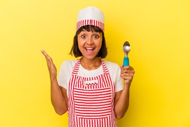 Giovane razza mista gelatiera donna tenendo un gelato scoop isolato su sfondo giallo