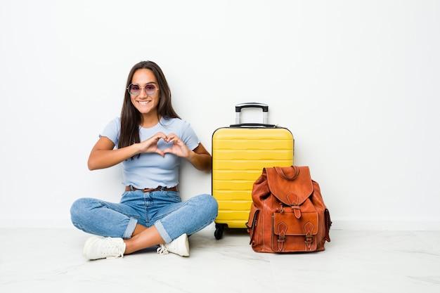 Giovane donna indiana di razza mista pronta ad andare a viaggiare sorridendo e mostrando una forma di cuore con le mani.