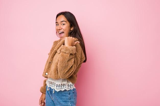 Giovane donna indiana di razza mista che indossa un cappotto corto di pelle di pecora con il pollice lontano, ridendo e spensierata.