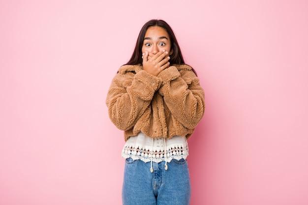 Giovane donna indiana di razza mista che indossa un cappotto di pelle di pecora corto che copre la bocca con le mani.