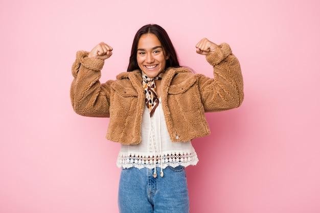 Giovane donna indiana di razza mista che indossa un corto cappotto di pelle di pecora che mostra un gesto di forza con le braccia, simbolo del potere femminile