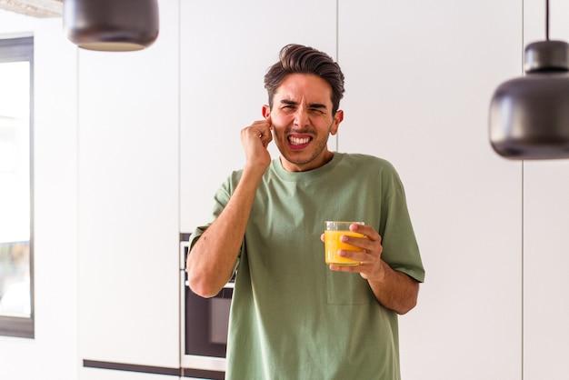 Giovane uomo di razza mista che beve succo d'arancia nella sua cucina che copre le orecchie con le mani.