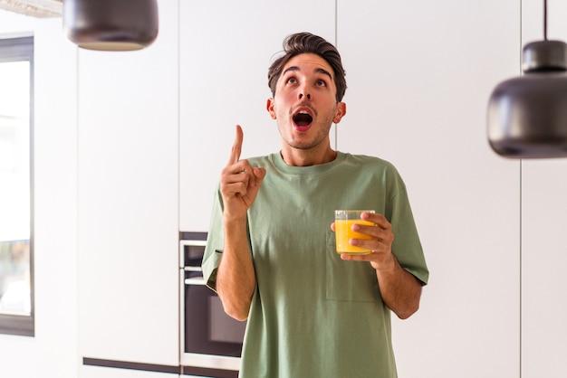 Giovane uomo di razza mista che beve succo d'arancia nella sua cucina che punta al rialzo con la bocca aperta.