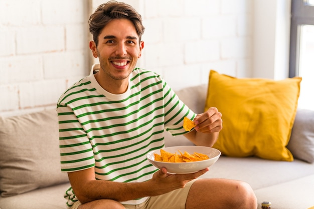 Giovane uomo di razza mista che mangia patatine seduto sul divano