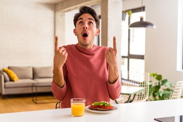 Giovane uomo di razza mista che fa colazione nella sua cucina puntando verso l'alto con la bocca aperta.