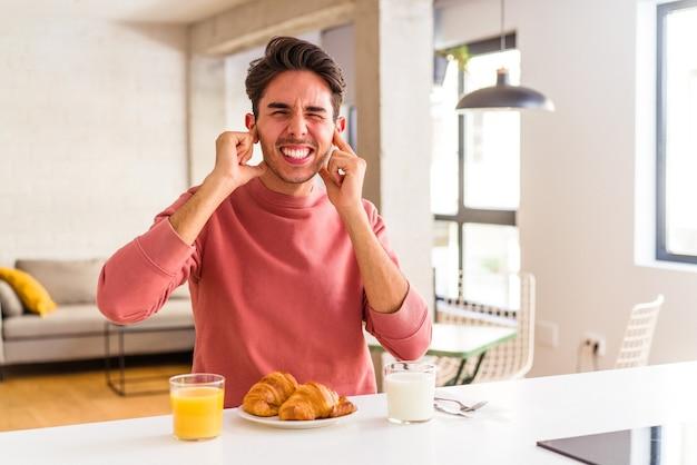 Giovane uomo di razza mista che fa colazione in cucina la mattina coprendosi le orecchie con le mani.