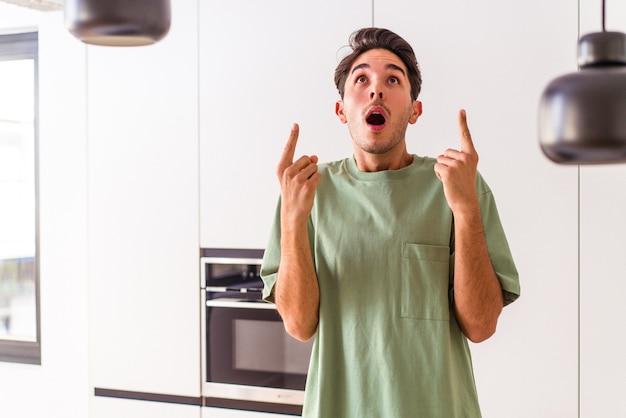 Giovane uomo di razza mista nella sua cucina che punta al rialzo con la bocca aperta.