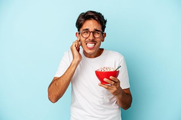 Giovane uomo di razza mista che tiene i cereali isolati su sfondo blu che copre le orecchie con le mani.