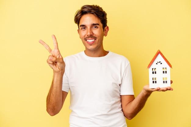 Giovane uomo di razza mista che tiene casa giocattolo isolata su sfondo giallo gioioso e spensierato che mostra un simbolo di pace con le dita.