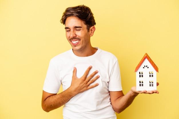 Giovane uomo di razza mista che tiene casa giocattolo isolata su sfondo giallo ridendo e divertendosi.