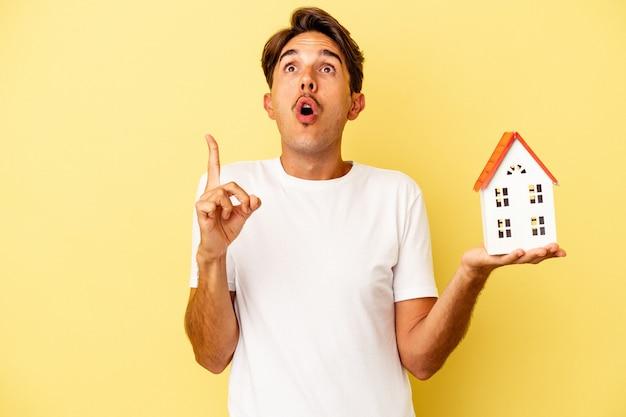 Giovane uomo di razza mista che tiene casa giocattolo isolata su sfondo giallo rivolto verso l'alto con la bocca aperta.