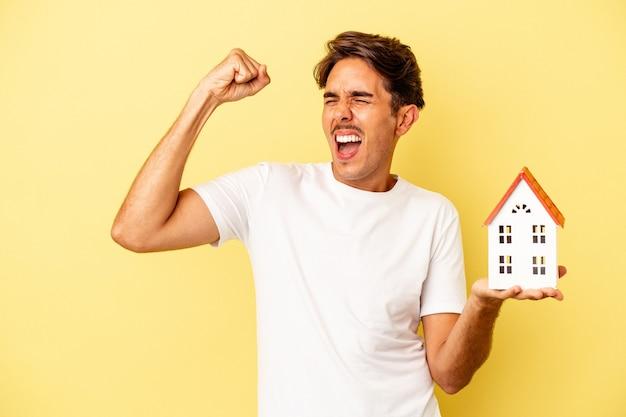 Giovane uomo di razza mista che tiene casa giocattolo isolata su sfondo giallo alzando il pugno dopo una vittoria, concetto di vincitore.