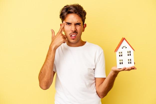 Giovane uomo di razza mista che tiene casa giocattolo isolata su sfondo giallo che mostra un gesto di delusione con l'indice.