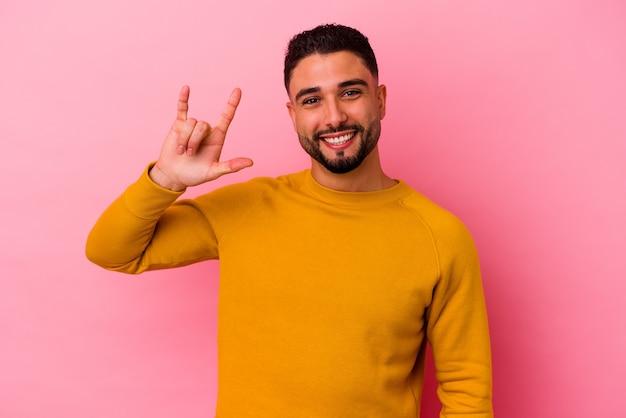 Giovane uomo di razza mista isolato su sfondo rosa che mostra un gesto di corna come un concetto di rivoluzione.