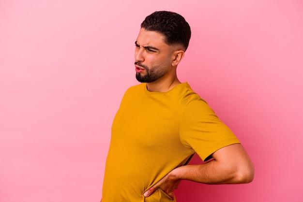 Giovane uomo di razza mista isolato su sfondo rosa che soffre di mal di schiena.