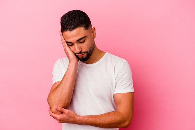 Giovane uomo di razza mista isolato su sfondo rosa che è annoiato, affaticato e ha bisogno di una giornata di relax.
